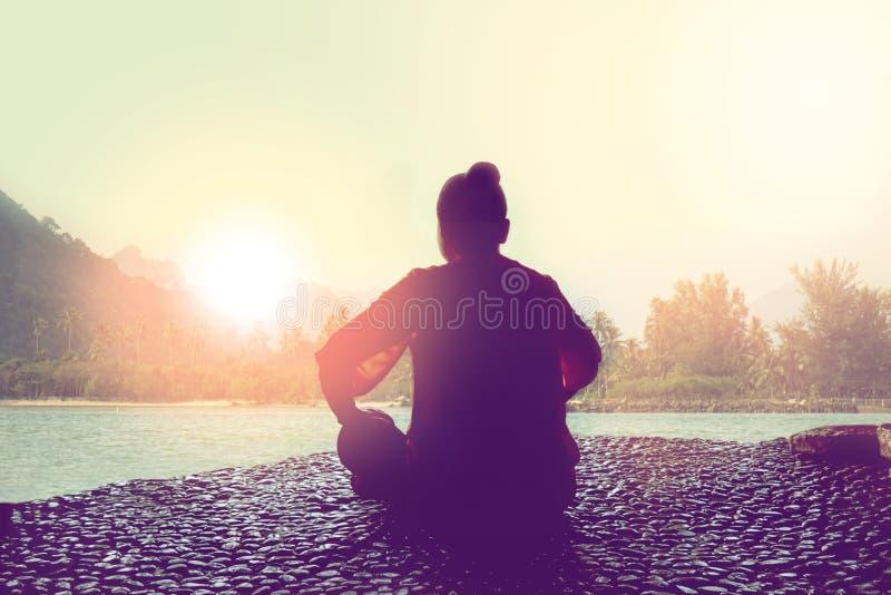 Sylwetka medytuje z wschód słońca kobieta zdjęcia stock