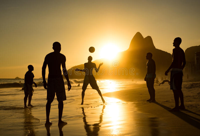 Sylwetka miejscowi bawić się piłkę przy zmierzchem w Ipanema plaży, Rio De Janeiro, Brazylia zdjęcie royalty free