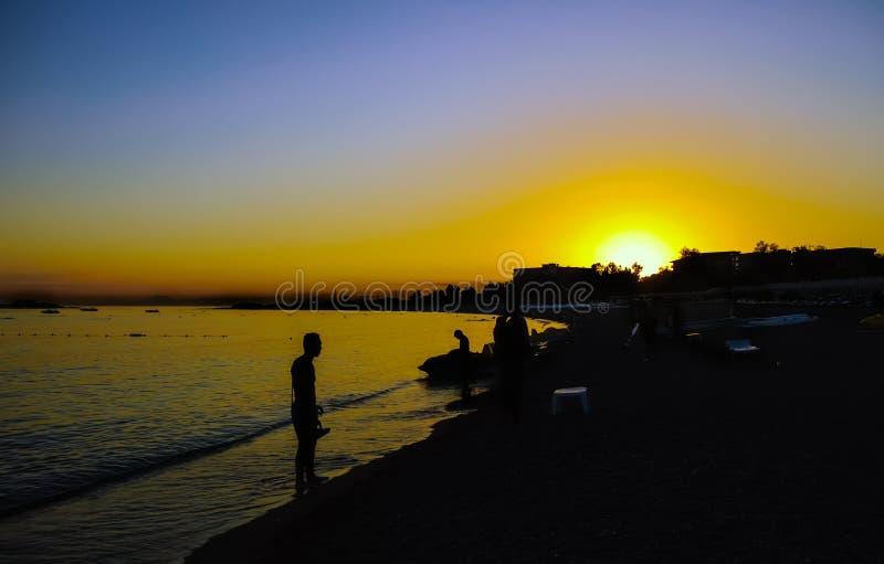 Sylwetka na plaży przy zmierzchem fotografia stock