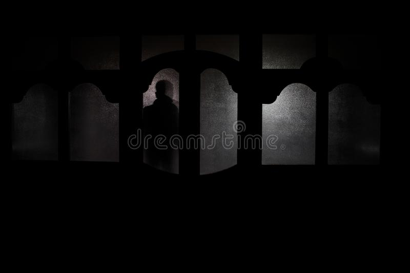 Sylwetka niewiadoma cień postać na drzwi przez zamkniętego szklanego drzwi Sylwetka istota ludzka przed okno przy ni royalty ilustracja