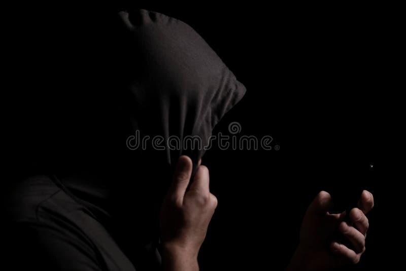 Sylwetka niewiadoma osoba w kapiszonie z telefonem komórkowym w ręce w zmroku zdjęcia stock