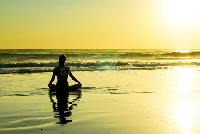 Sylwetka niewiadomy unrecognizable kobiety obsiadanie na plażowej wody morskiej ćwiczy joga i medytacja patrzeje słońce na hor zdjęcia royalty free