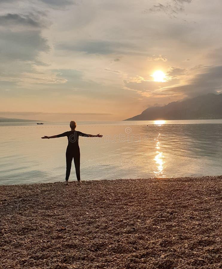 Sylwetka nikła kobieta patrzeje zmierzch który stoi na seashore, Cieszyć się relaksującego wakacje obraz stock