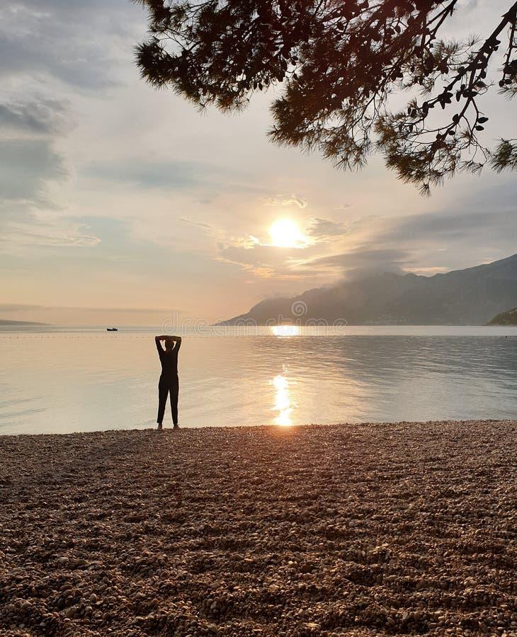 Sylwetka nikła kobieta patrzeje zmierzch który stoi na seashore, Cieszyć się relaksującego wakacje obraz royalty free