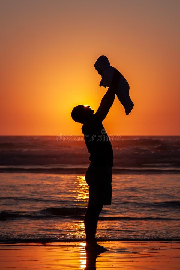 Sylwetka ojciec trzyma dziecka w górę wysokości na plaży przy zmierzchem zdjęcia royalty free