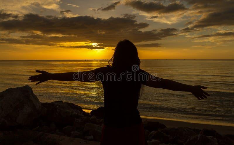 Sylwetka ono modli się nad pięknym zmierzchem kobieta obraz royalty free