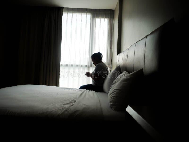 Sylwetka osamotniona Wzburzony kobiety obsiadanie używać telefon w łóżku, samotnie fotografia royalty free