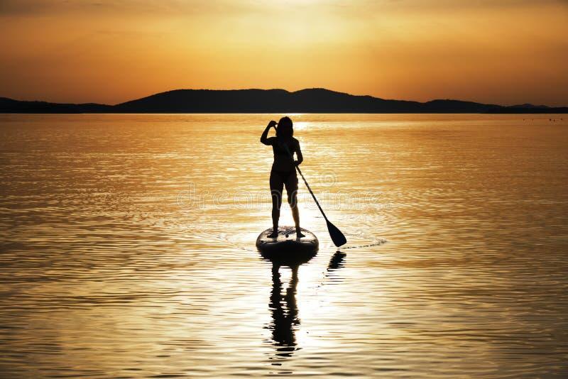 Sylwetka paddling przy zmierzchem na stojaku w górę paddleboard SUP w Chorwacja kobieta, Adriatycki morze, blisko Sibenik b??kitn obrazy royalty free