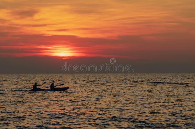 Sylwetka pary kayaking w morzu przy zmierzchem Kajak w tropikalnym morzu przy zmierzchem Romantyczna pary podróż na lecie obraz royalty free