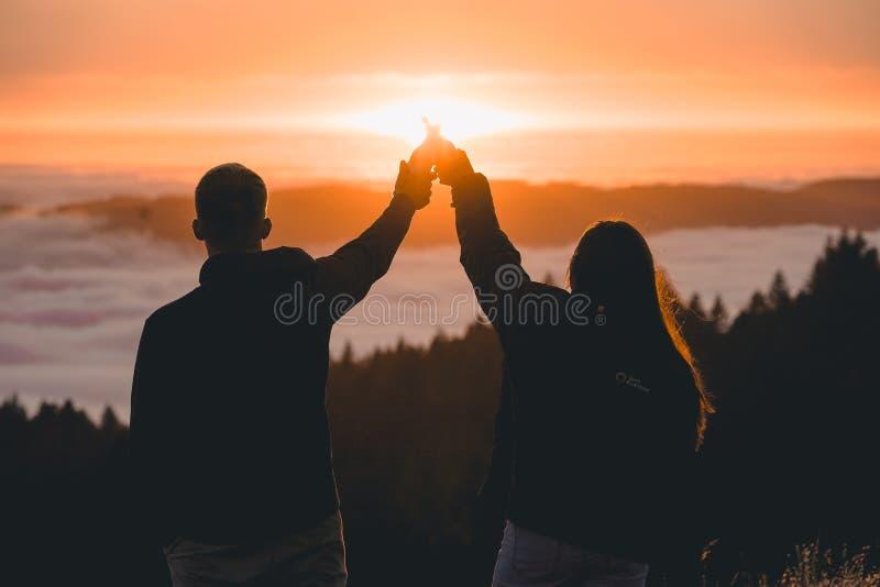 Sylwetka pary mienia ręki i pozycja dalej nakrywamy halnego Tama blisko morza przy zmierzchem zdjęcia stock