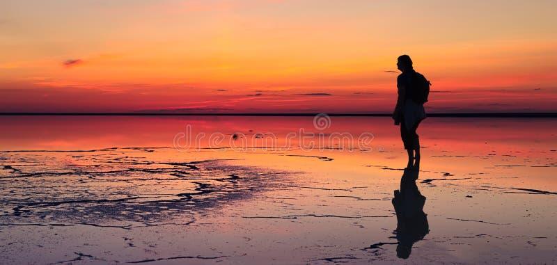 Sylwetka patrzeje w kierunku wibrującego zmierzchu odbijającego w płytkim samotny mężczyzna nawadnia solt jezioro obrazy royalty free