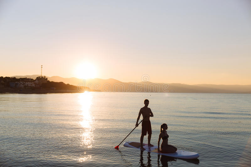 Sylwetka perfect para angażuje standup paddle abordaż obraz royalty free