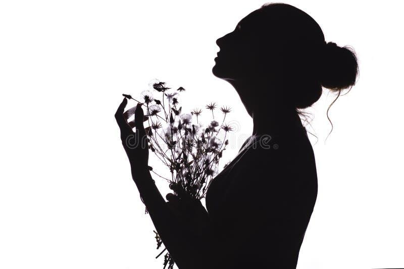 Sylwetka piękna dziewczyna z bukietem wysuszeni kwiaty, twarzy młoda kobieta patrzeje upwards na biały odosobnionym profil zdjęcia royalty free