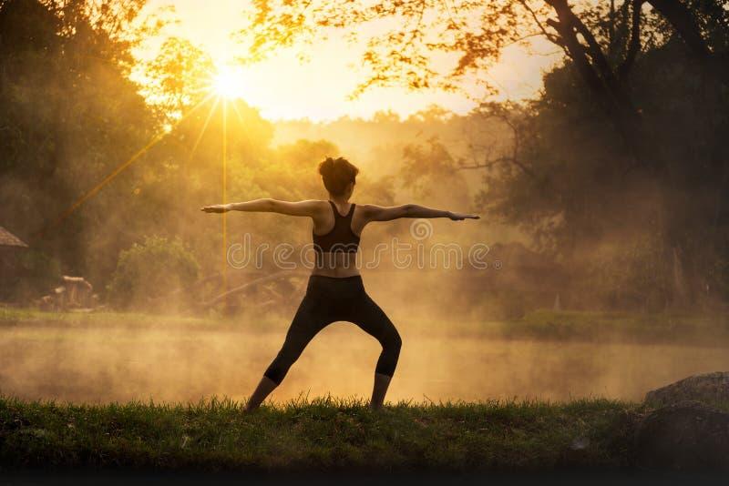 Sylwetka piękna joga kobieta w ranku przy gorącej wiosny parkiem fotografia royalty free