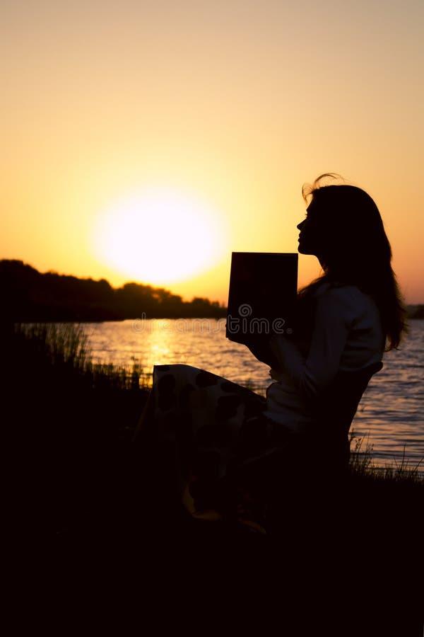 Sylwetka piękna młoda kobieta odbija na informaci czyta wewnątrz książkę na naturze obraz royalty free