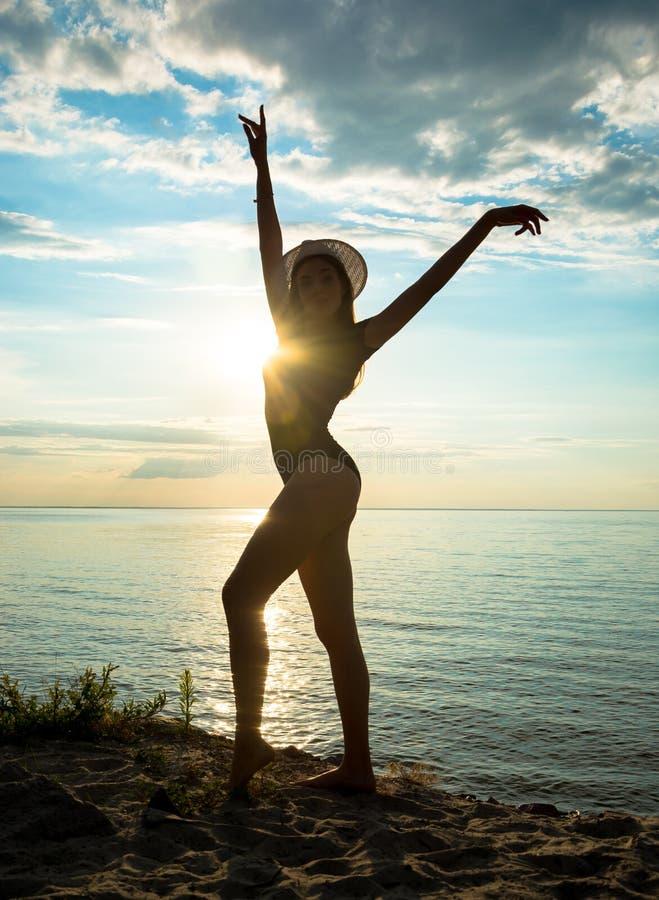 Sylwetka piękna młoda kobieta stoi w swimsuit który obrazy royalty free