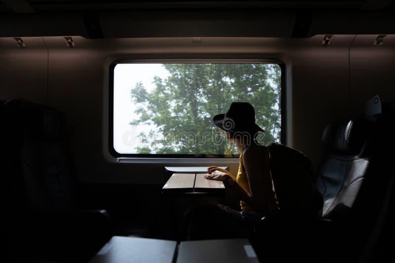Sylwetka pięknego modnisia azjatykcia kobieta podróżuje na pociągu zdjęcie royalty free