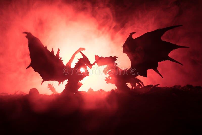 Sylwetka pożarniczy oddychanie smok z dużymi skrzydłami na zmroku - pomarańczowy tło ilustracji