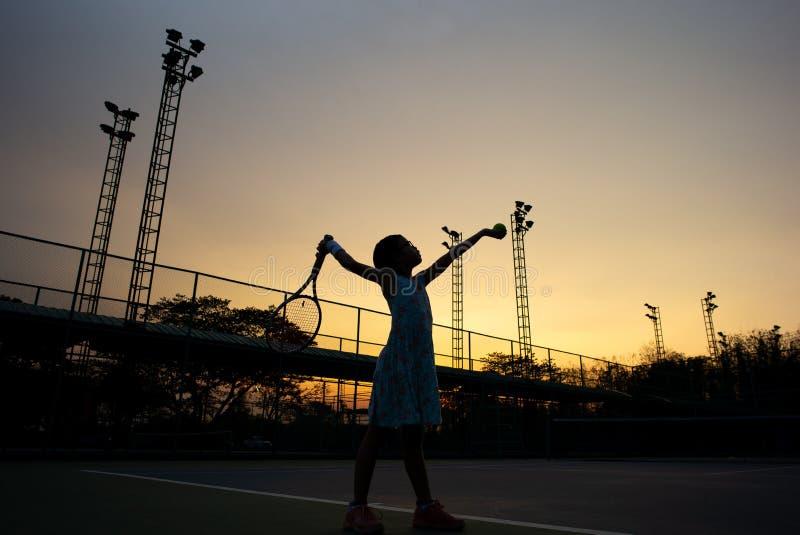 Sylwetka portret Azjatycka dziewczyna bawić się tenisa przy plenerowym sądem z zmierzchu niebem w tle zdjęcia stock