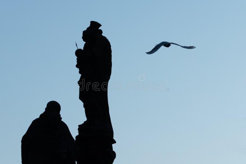Sylwetka posągu na moście Karola w Pradze, z ptakiem latającym. Mostek gotycki średniowieczny zakończony w XV wieku, przejśc obraz royalty free
