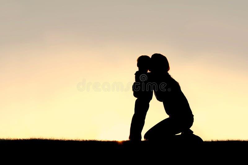 Sylwetka potomstwa przytulenia berbecia Macierzysty syn przy zmierzchem zdjęcie royalty free