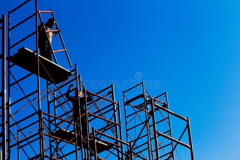 Sylwetka pracownicy budowlani przeciw niebu na rusztować wi obrazy royalty free