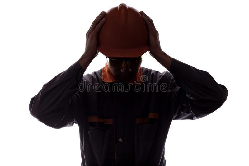 Sylwetka pracownika budowlanego cierpienie od migreny i hałas, mężczyzna w hełmie na białym odosobnionym tle obraz stock
