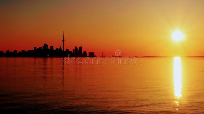 Sylwetka przeciwstawiająca powstający słońce nad Jeziornym Ontario Toronto's linia horyzontu fotografia stock