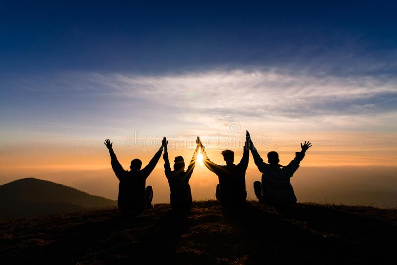 Sylwetka przyjaciele trząść ręki up i siedzący wpólnie w słońcu fotografia royalty free
