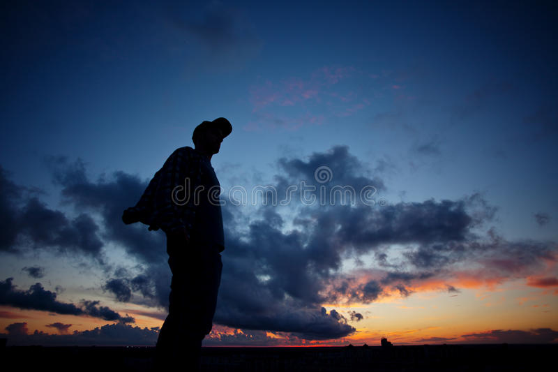 Sylwetka przypadkowa mężczyzna pozycja na górze dachu w mieście przy zmierzchem zdjęcie royalty free