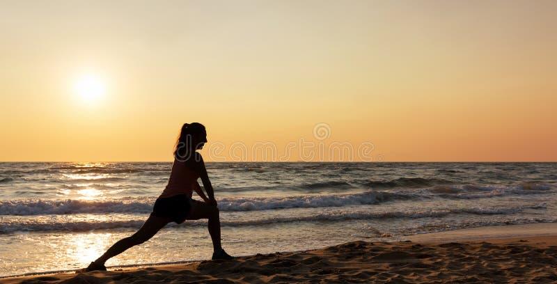 Sylwetka robi ćwiczeniu na plaży kobieta obraz royalty free