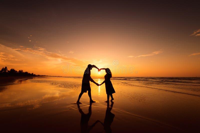 Sylwetka robi kierowemu kształtowi z rękami na plaży przy zmierzchem para zdjęcie royalty free