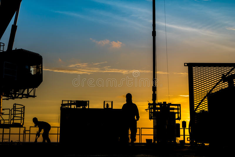 Sylwetka ropa i gaz wellhead platforma i well usługowy pracownik podczas gdy pracujący dziurkowanie produkci tubingu gazu rezerwu zdjęcia stock