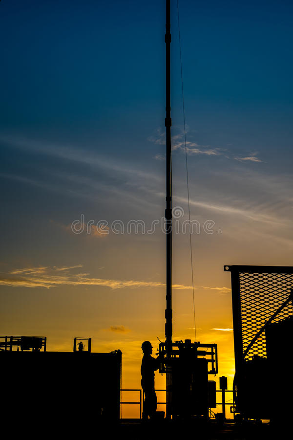 Sylwetka ropa i gaz wellhead platforma i well usługowy pracownik podczas gdy pracujący dziurkowanie produkci tubingu gazu rezerwu obrazy stock