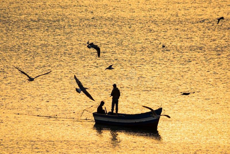 Sylwetka rybacy łódkowaci na morzu śródziemnomorskim podczas wschód słońca w złotych słońce promieniach w Maroko obraz stock