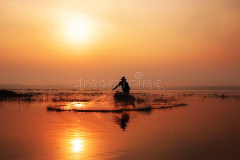 Sylwetka rybacy ciska dla łapać ryba na zalecającym się zdjęcie stock