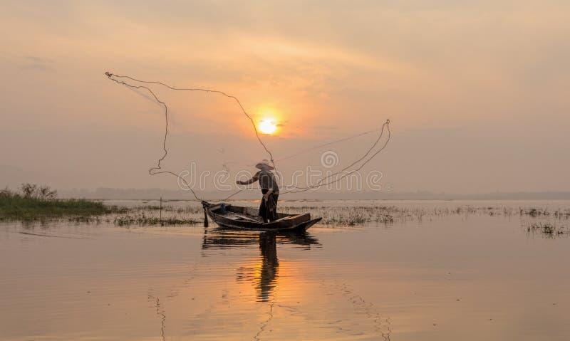 Sylwetka rybacy ciska dla łapać ryba na zalecającym się zdjęcie royalty free