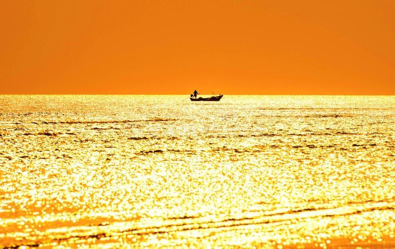 Sylwetka rybacy na łodzi rybackiej w morzu I evenin zdjęcie stock