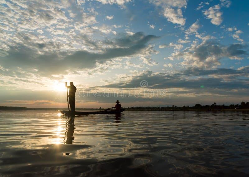 Sylwetka rybacy rzuca netto połów w zmierzchu czasie przy W fotografia stock