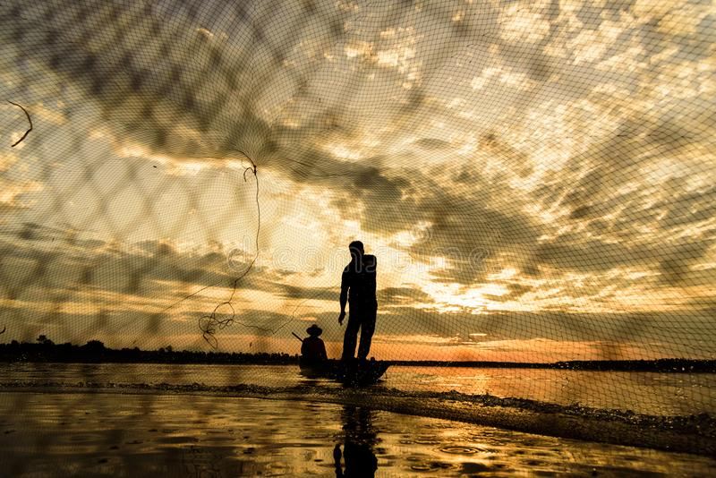 Sylwetka rybacy z zmierzchu czasem przy Wanon Niwat okręgiem zdjęcia royalty free