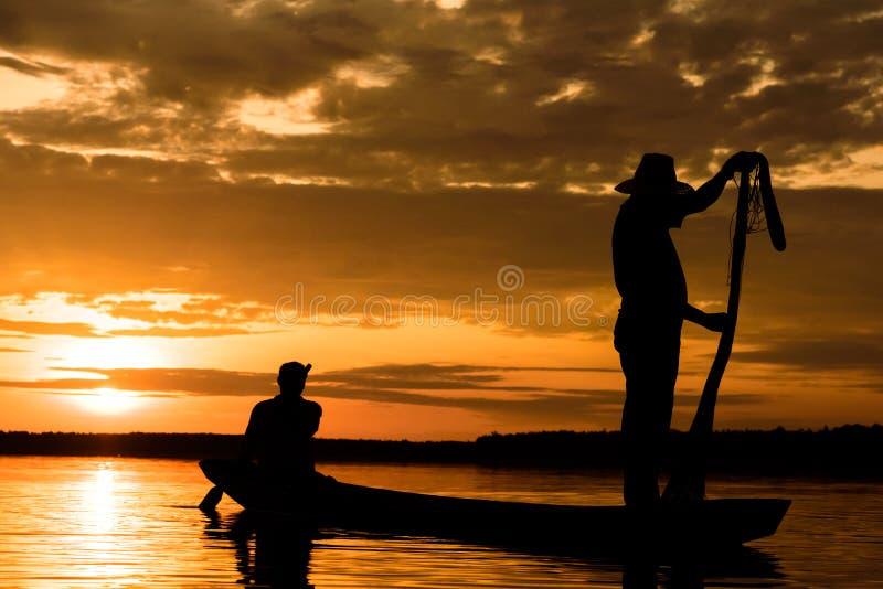 Sylwetka rybacy z zmierzchu czasem przy Wanon Niwat okręgiem fotografia royalty free