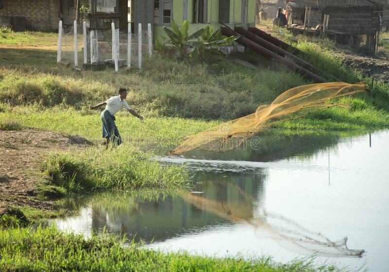 Sylwetka rybak rzuca fishnet w jeziorze zdjęcia stock