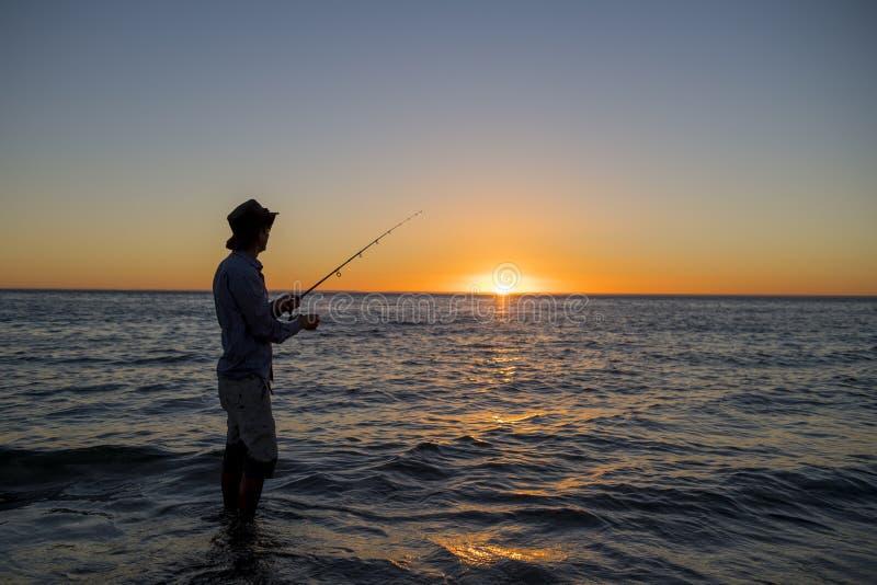 Sylwetka rybak z kapeluszem na plaży z rybią prącie pozycją na woda morska połowie przy zmierzchem z pięknym pomarańczowym niebem zdjęcia stock