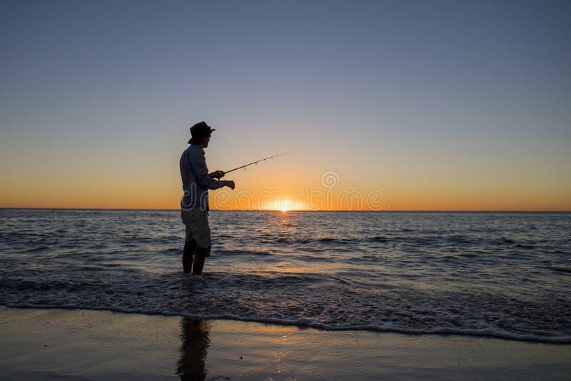 Sylwetka rybak z kapeluszem na plaży z rybią prącie pozycją na woda morska połowie przy zmierzchem z pięknym pomarańczowym niebem obraz stock