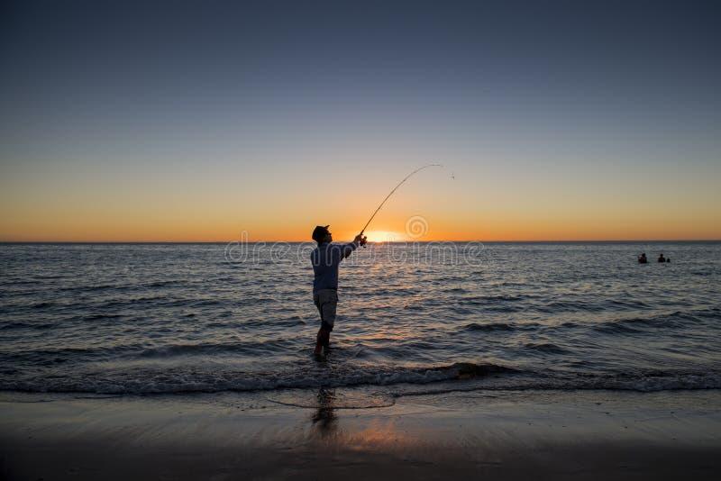 Sylwetka rybak z kapeluszem na plaży z rybią prącie pozycją na woda morska połowie przy zmierzchem z pięknym pomarańczowym niebem obraz royalty free