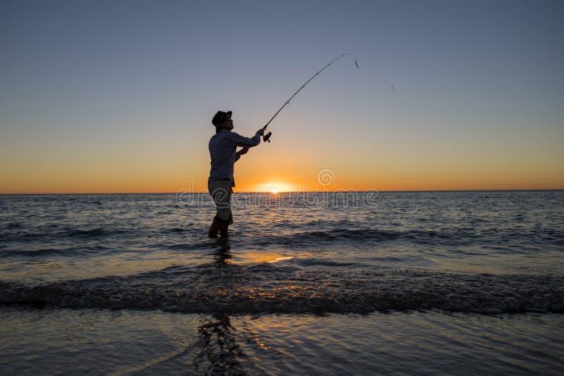 Sylwetka rybak z kapeluszem na plaży z rybią prącie pozycją na woda morska połowie przy zmierzchem z pięknym pomarańczowym niebem zdjęcie stock