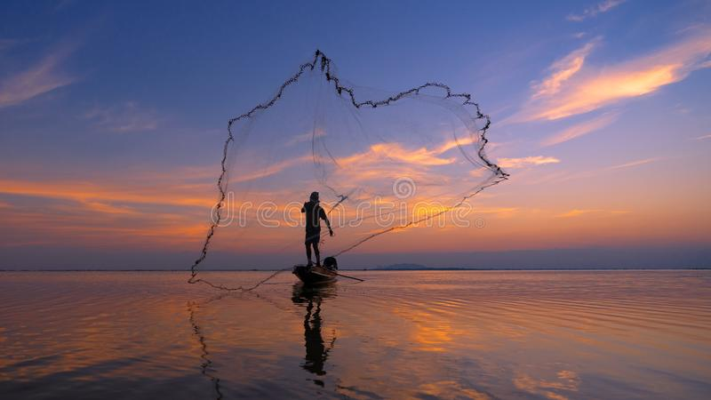 Sylwetka rybaka sieci rybackie na ?odzi Sylwetka rybacy używa jak oklepa łapania ryba w jeziorze z pięknym s zdjęcie royalty free
