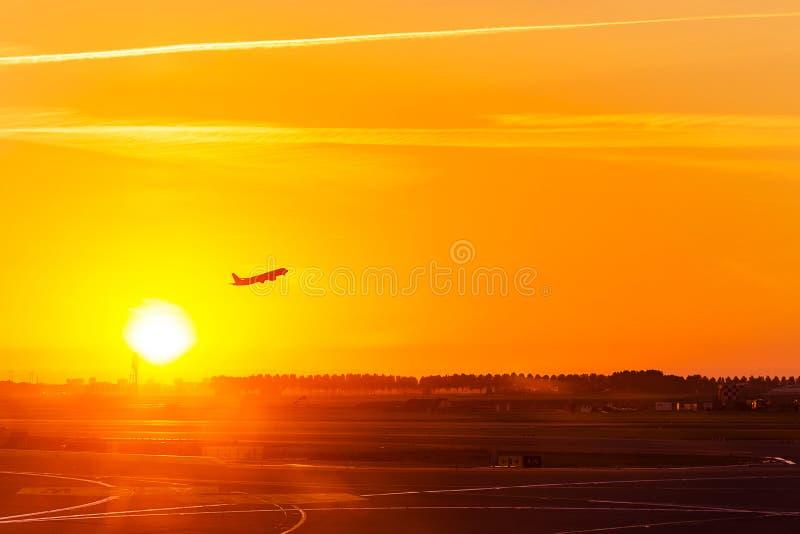 Sylwetka samolot, samolot, zdejmuje na powietrzu przy zmierzchu czasem w zdjęcia stock