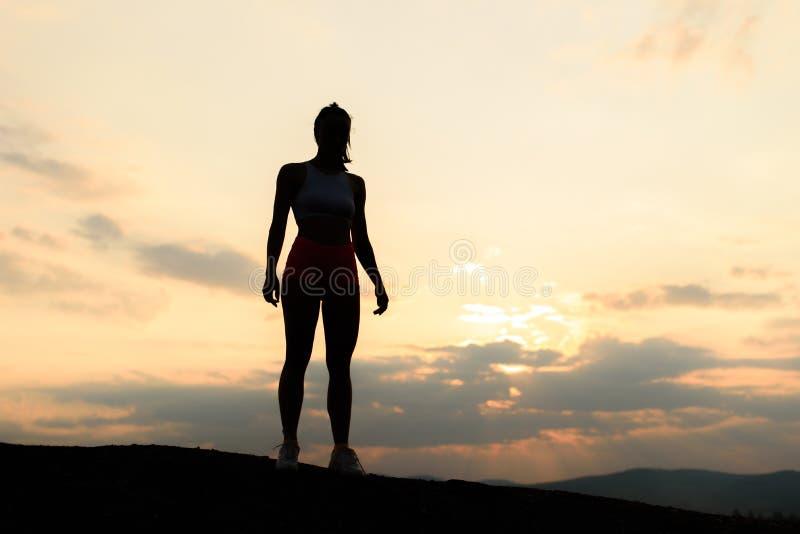 Sylwetka silna i ufna mięśniowa kobieta na zmierzchu zdjęcie stock