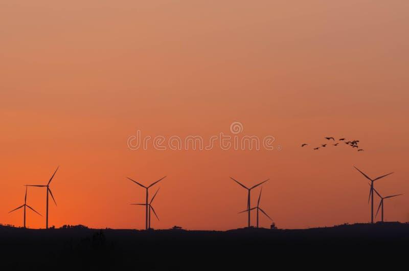 Sylwetka silników wiatrowych władzy generator na wzgórzu obrazy royalty free